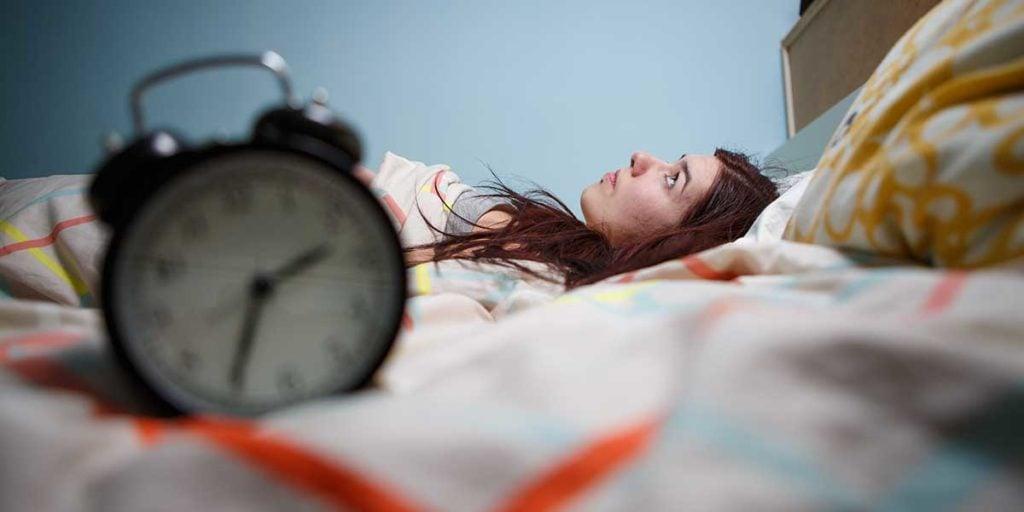 vrouw ligt wakker in bed