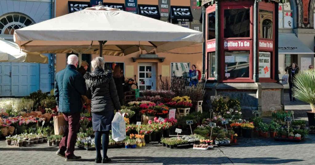 Koppel op leeftijd staat voor een bloemenwinkel op een zonnige dag