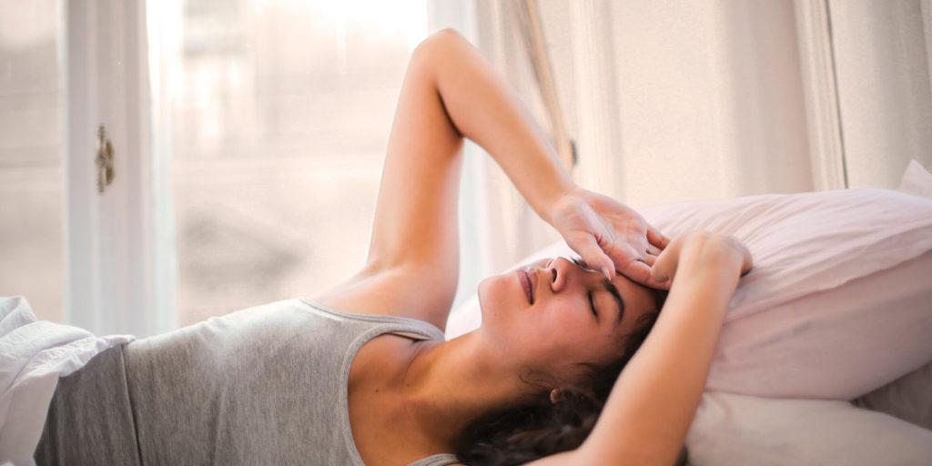 vrouw in bed met hoofdpijn